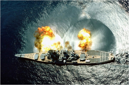 Ondas de Choque Esféricas generadas por la detonación de los cañones del USS Iowa. Claramente se visualiza el impacto de las ondas de choque en la superficie del océano. (fotografía oficial de US Navy, USNHC # DN-ST-85-05379, POR PHAN J. Alan Elliott, tomado de www.navsource.org/archives/01/61h.htm)
